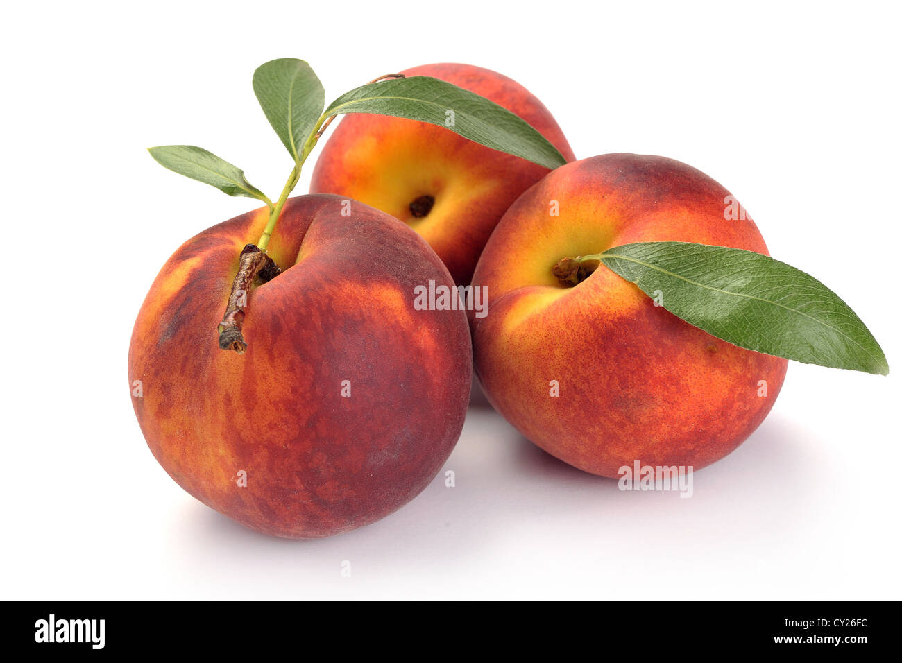 peach and leaves on a white background - Stock Image
