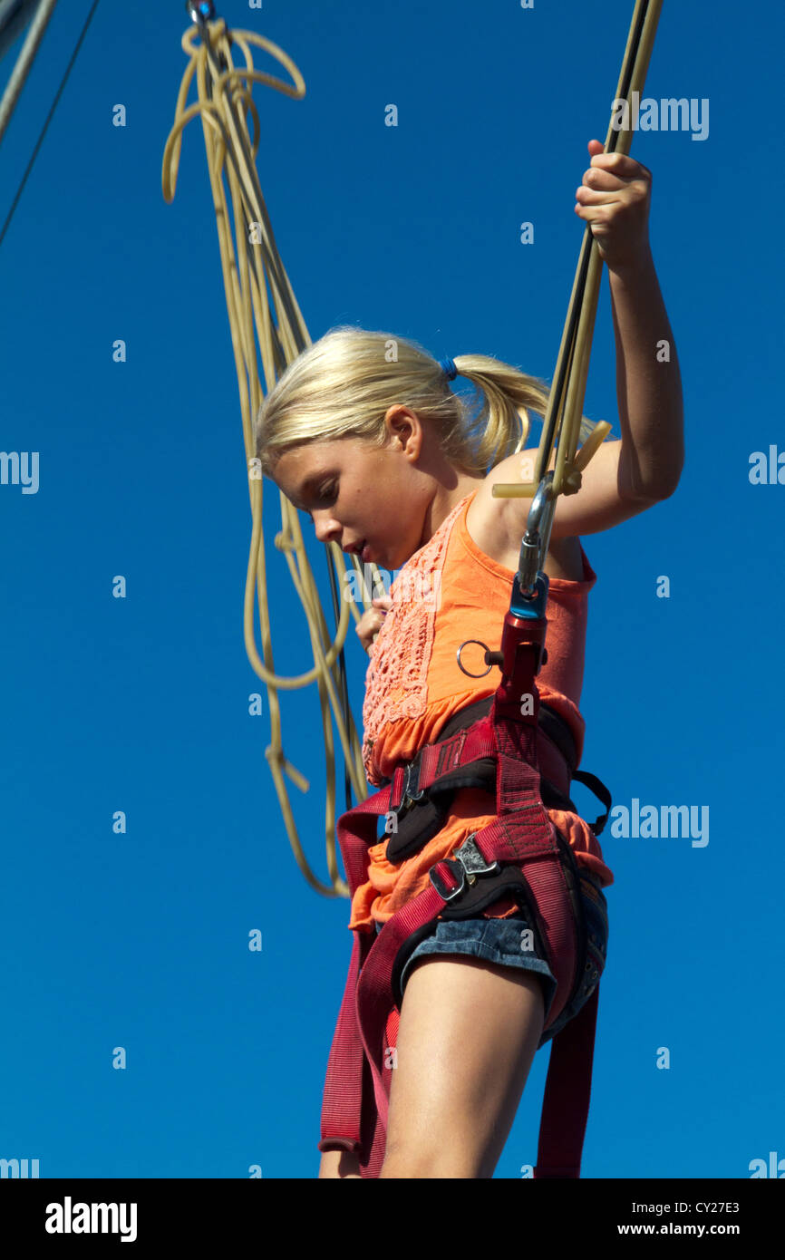 Young girl bounces on bungee cord - Stock Image