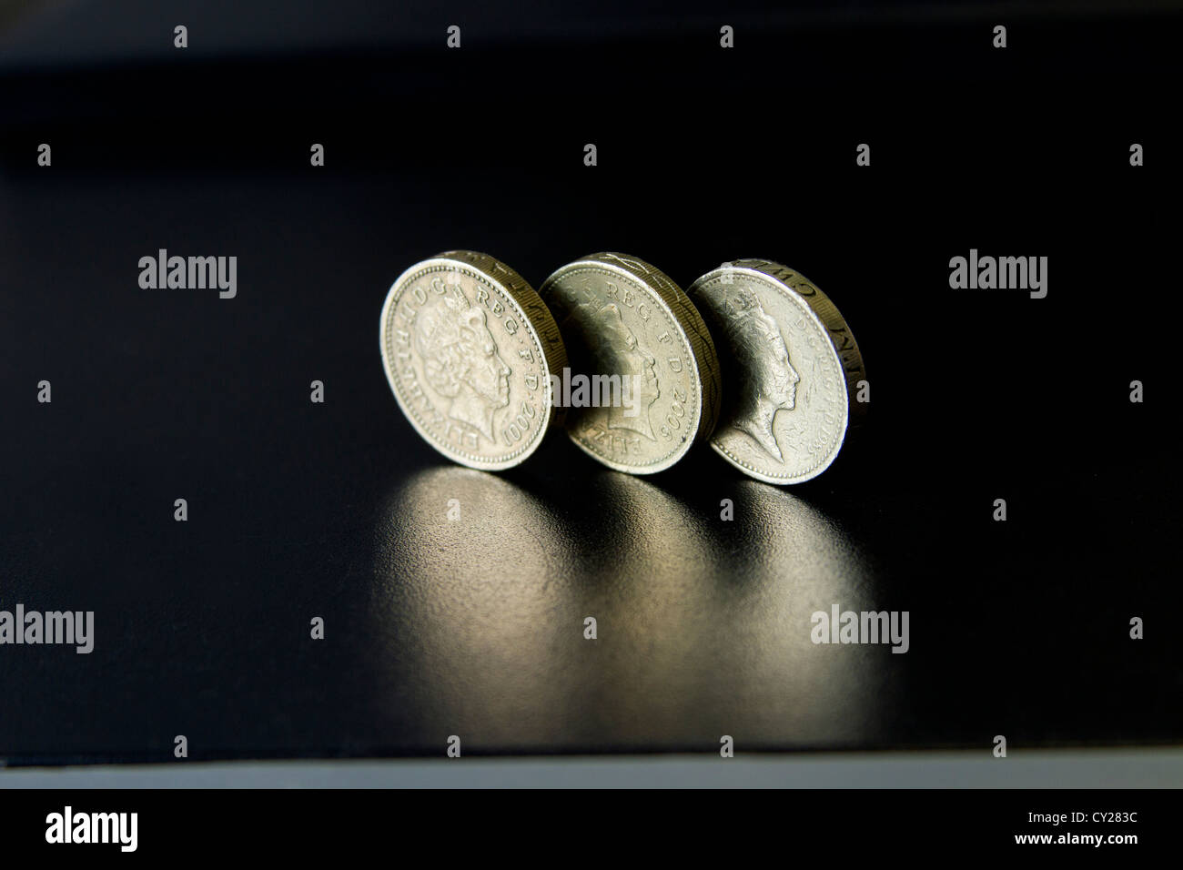 Three UK pounds side to side on a reflective black surface - Stock Image
