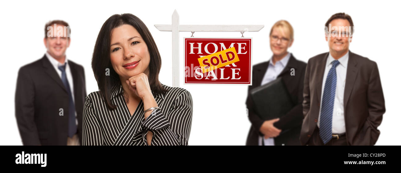 Pretty Hispanic Woman and Other People Behind in Front of Sold Home For Sale Real Estate Sign Isolated on a White - Stock Image