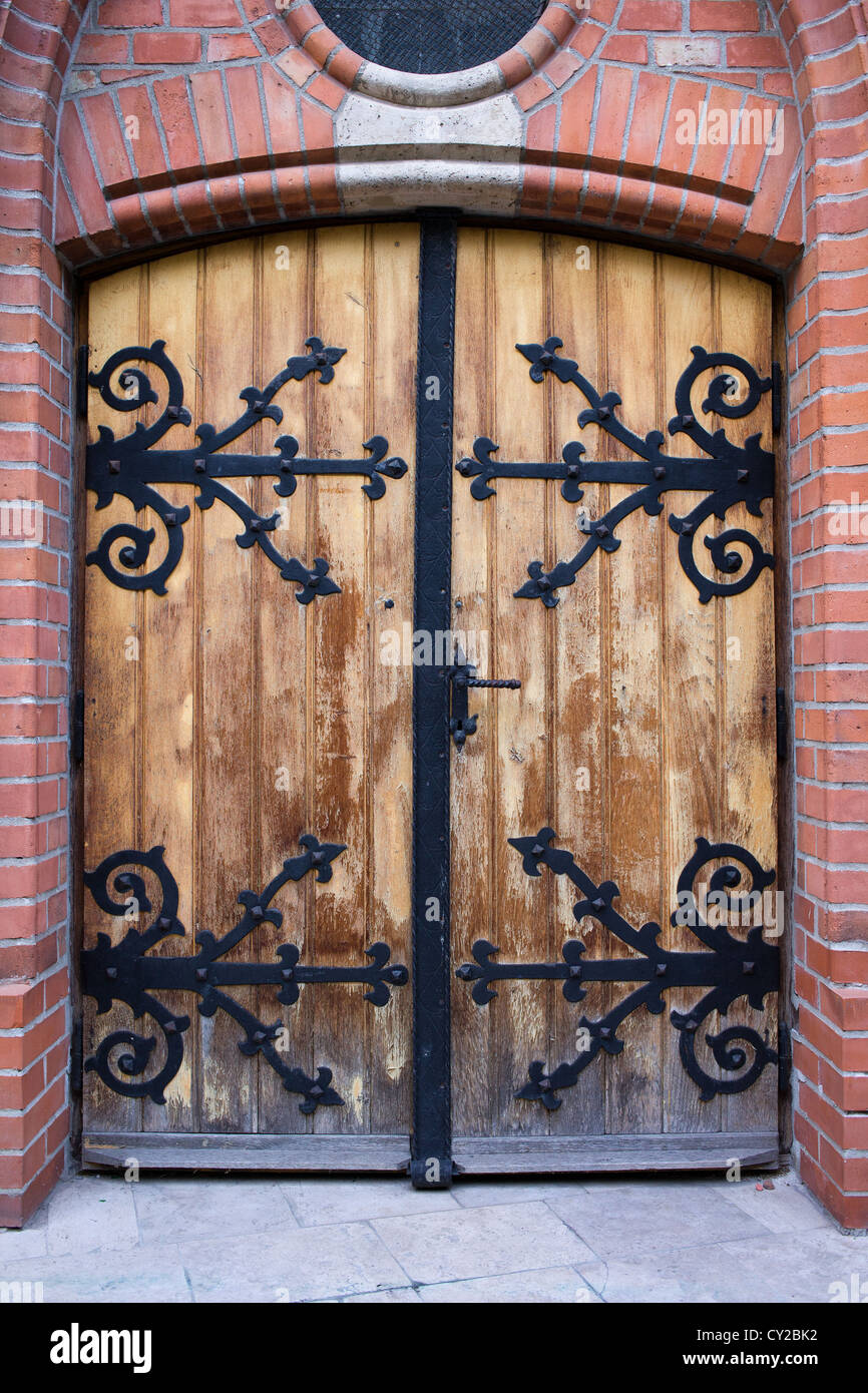 An old antique wooden door with wrought iron ornate reinforcement in ...