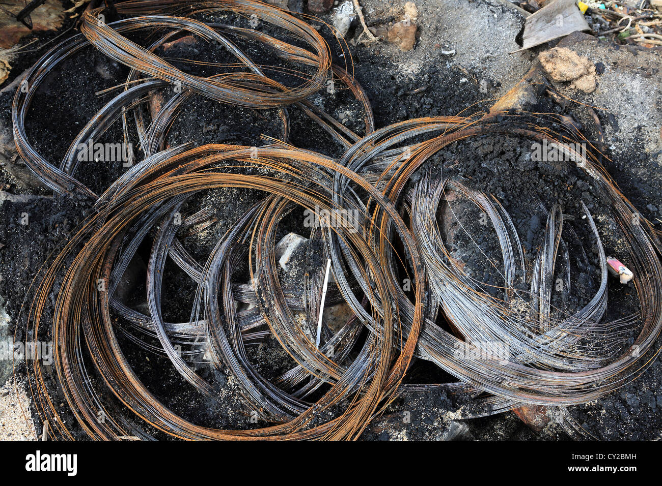 Steel wire remains of burnt out vehicle tires on Sri Lankan beach - Stock Image