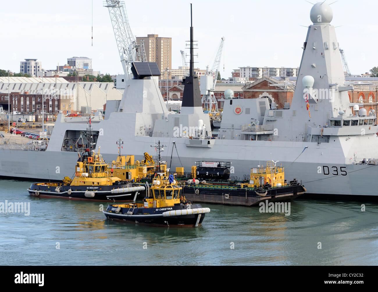 Tug boats round a warship. Portsmouth harbour.  Portsmouth, Hampshire, UK. - Stock Image