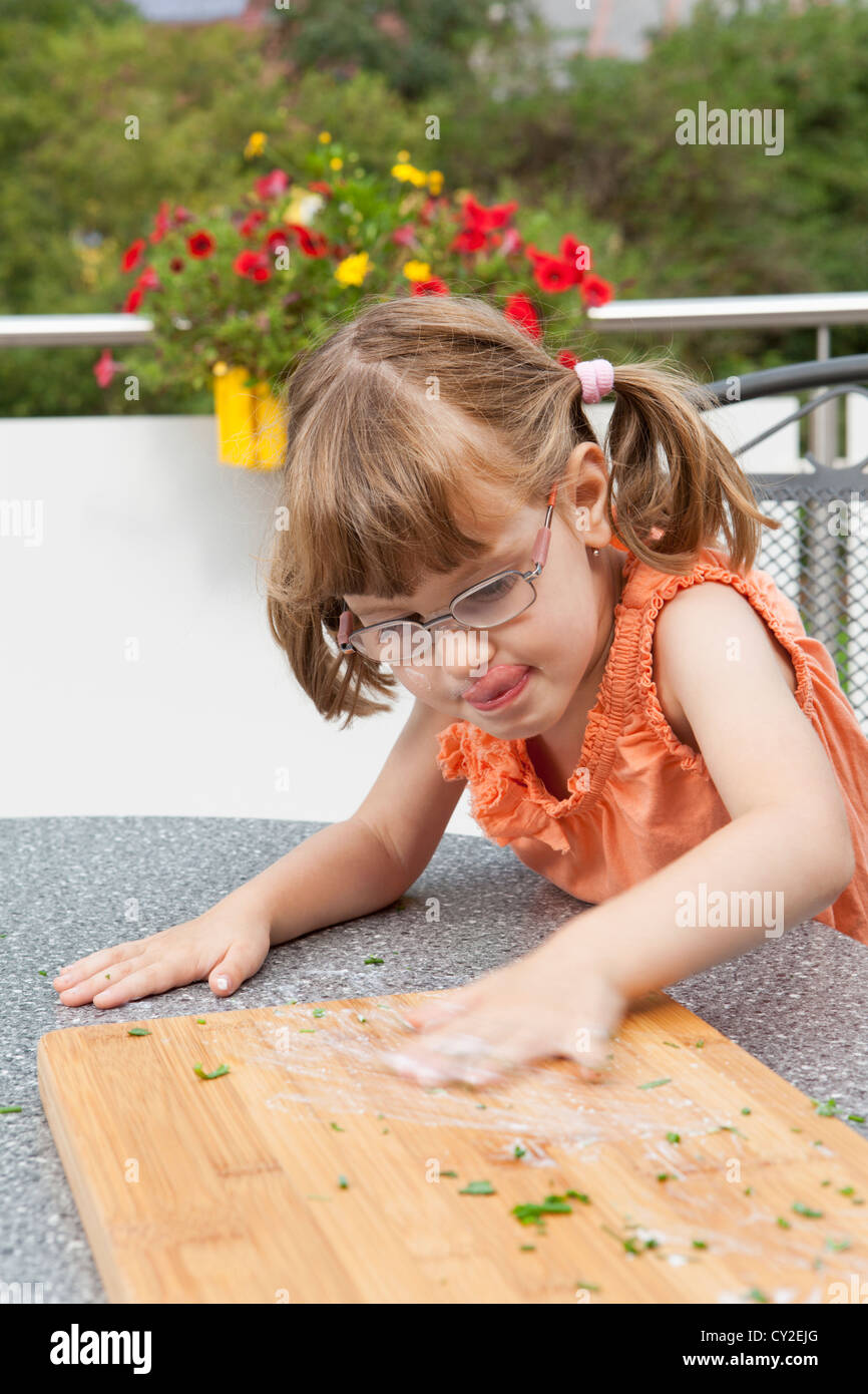 Girl blurs sauce on the cutting board Stock Photo