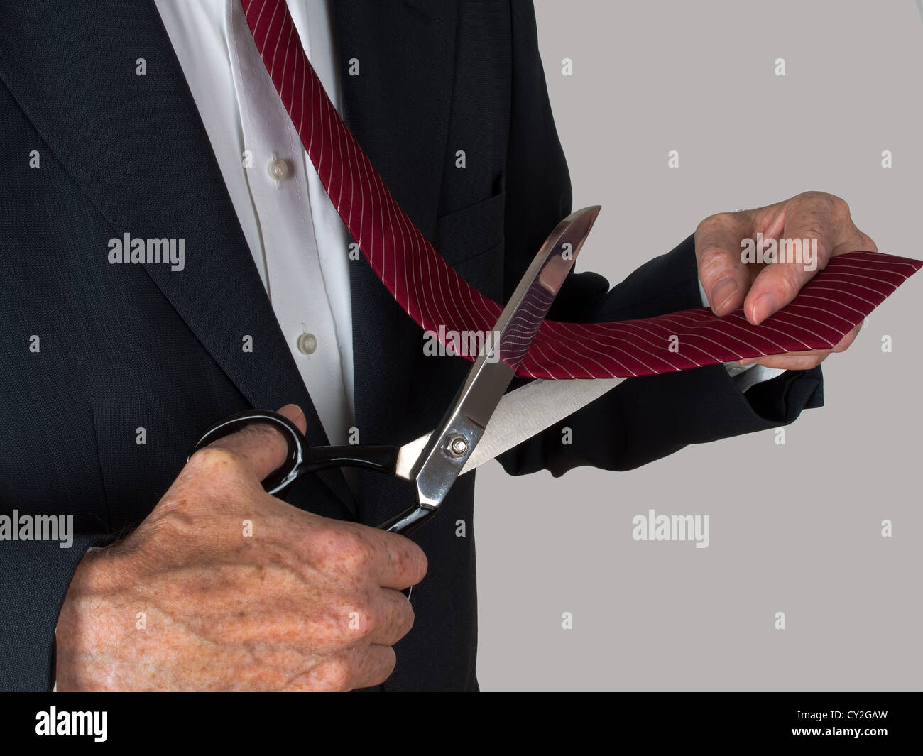 Quitting business - man cutting own tie - Stock Image