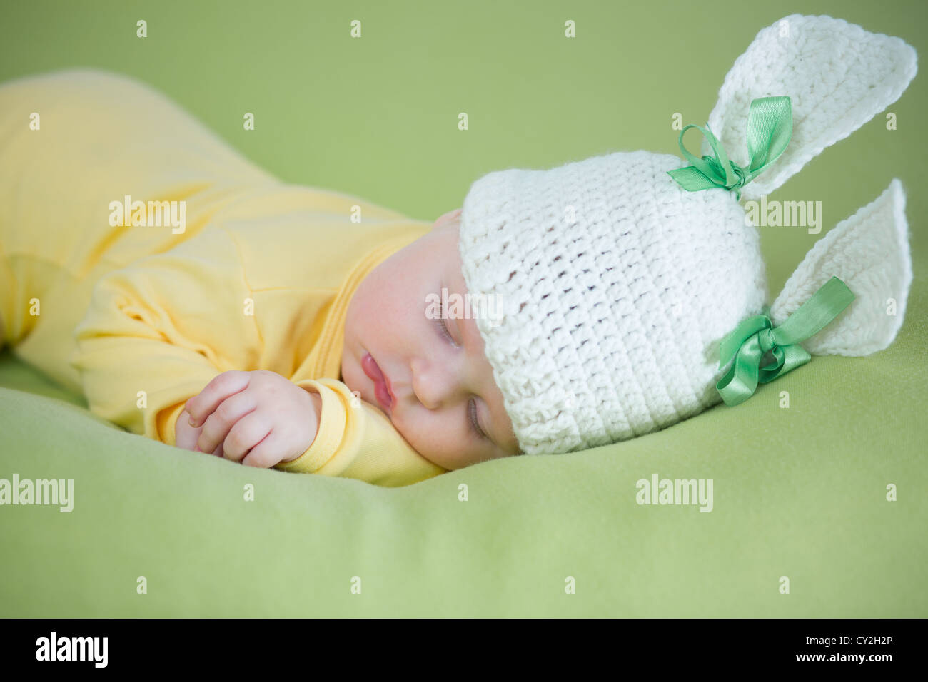 sleeping bunny baby in funny hat on green background