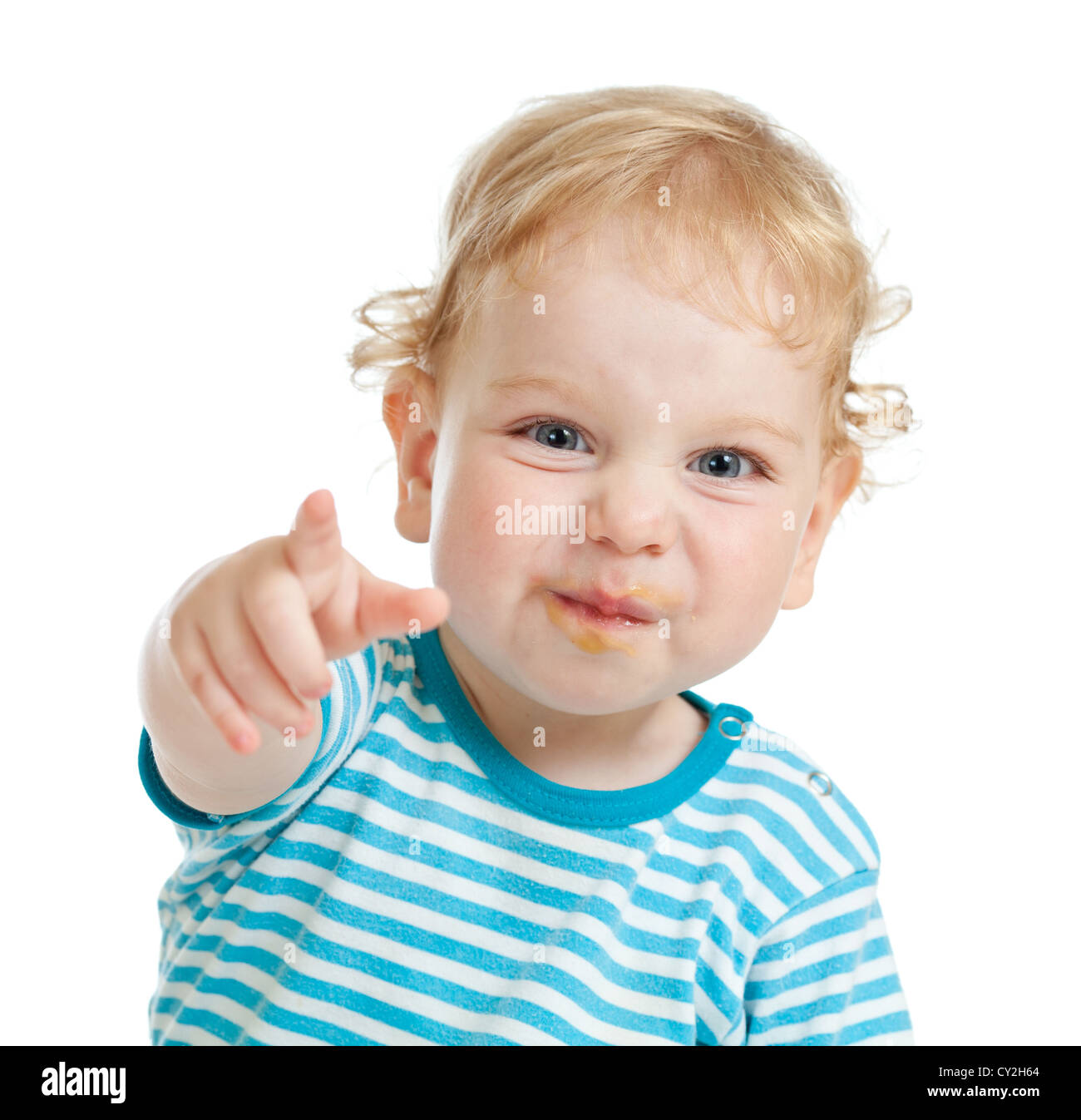funny curly child with dirty lips pointing by finger directly to camera - Stock Image