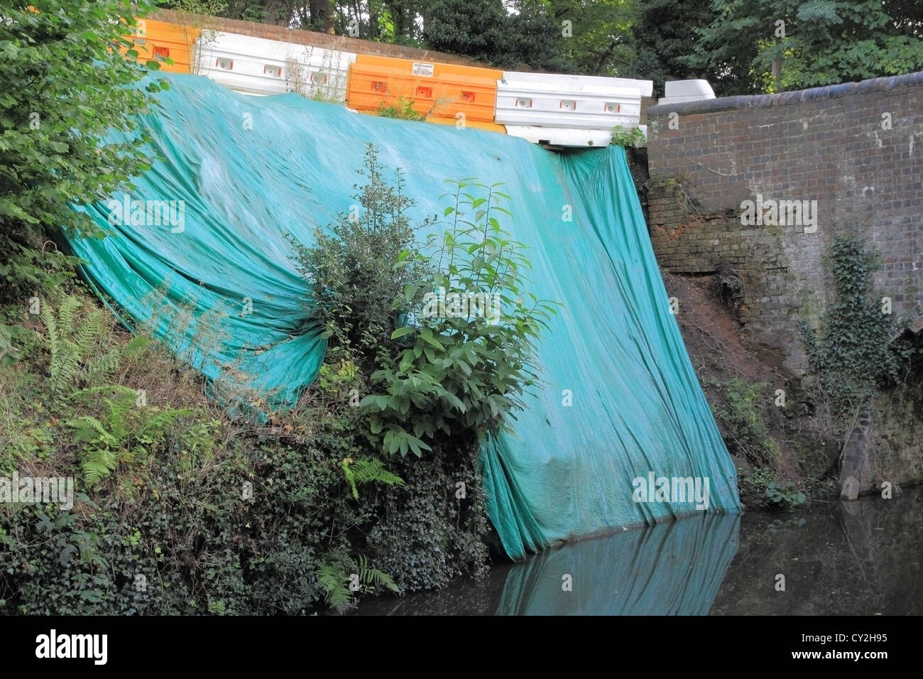 Green Tarpaulin draped over an embankment following a landslip on the Staffordshire & Worcestershire Canal, - Stock Image