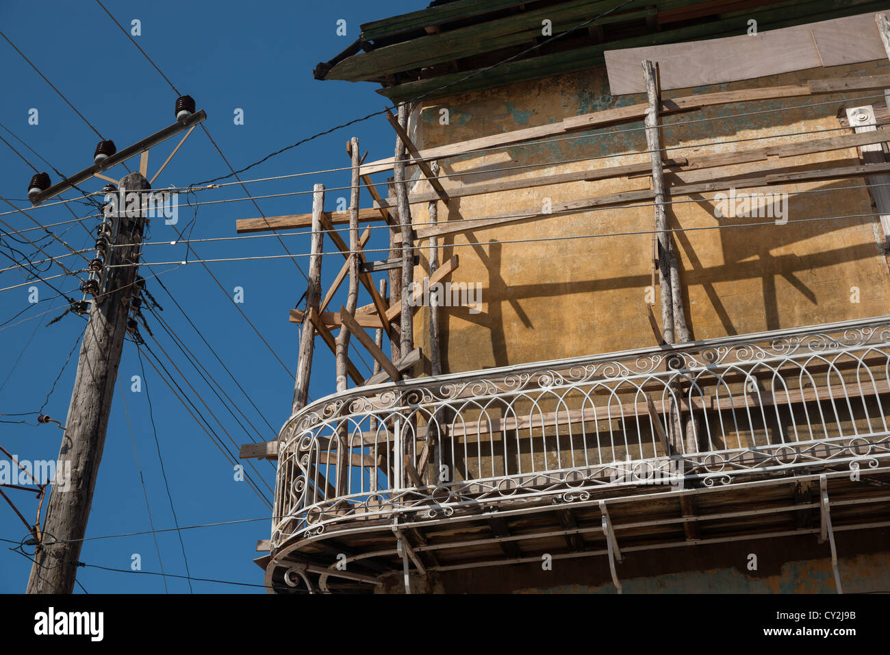 Rustic Cuban building under repair veranda and scaffolding near overheadpower pole and lines. - Stock Image
