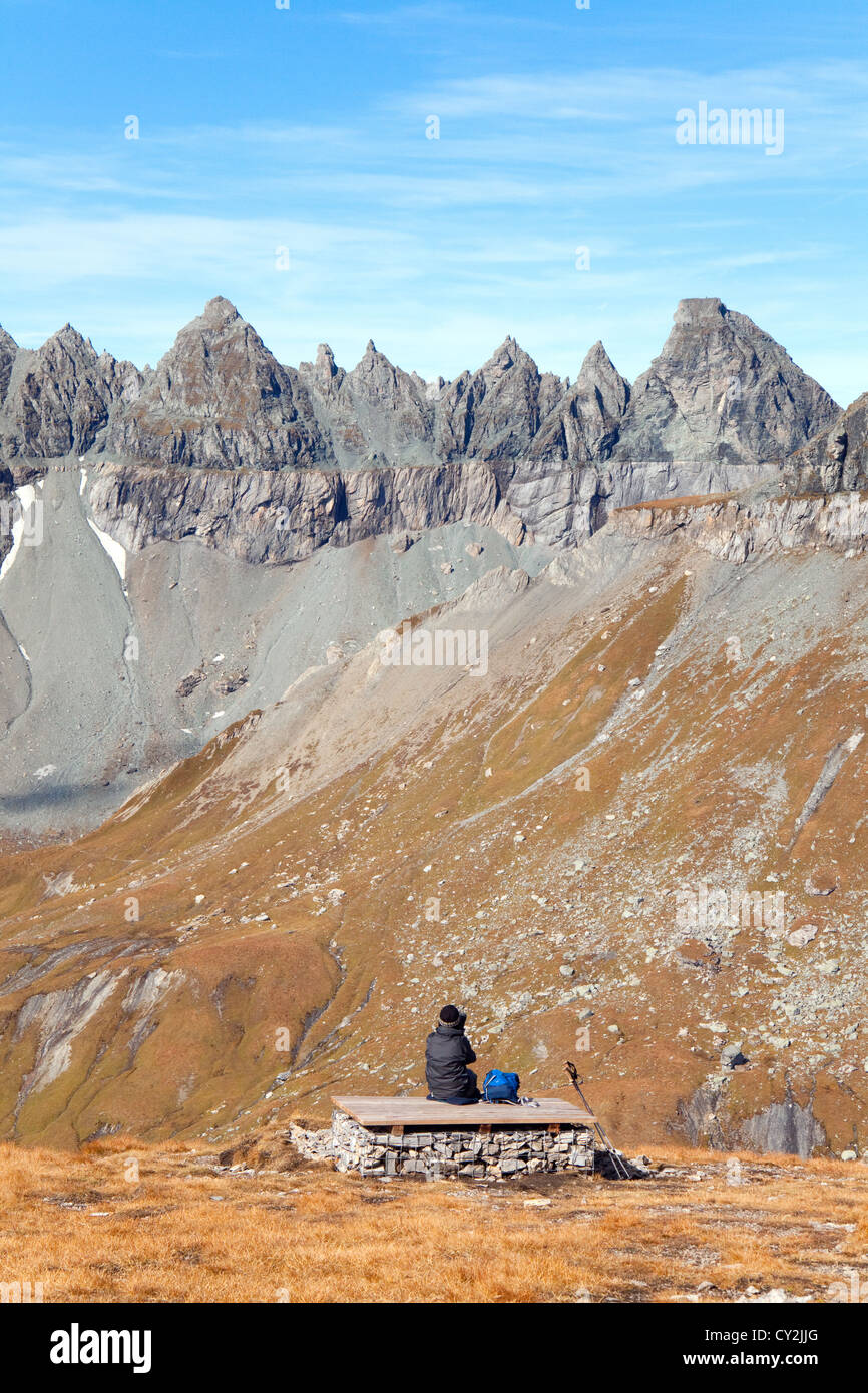 A walker looking at the Glarus Thrust World Heritage Site, Swiss Alps at Flims, Switzerland Europe - Stock Image