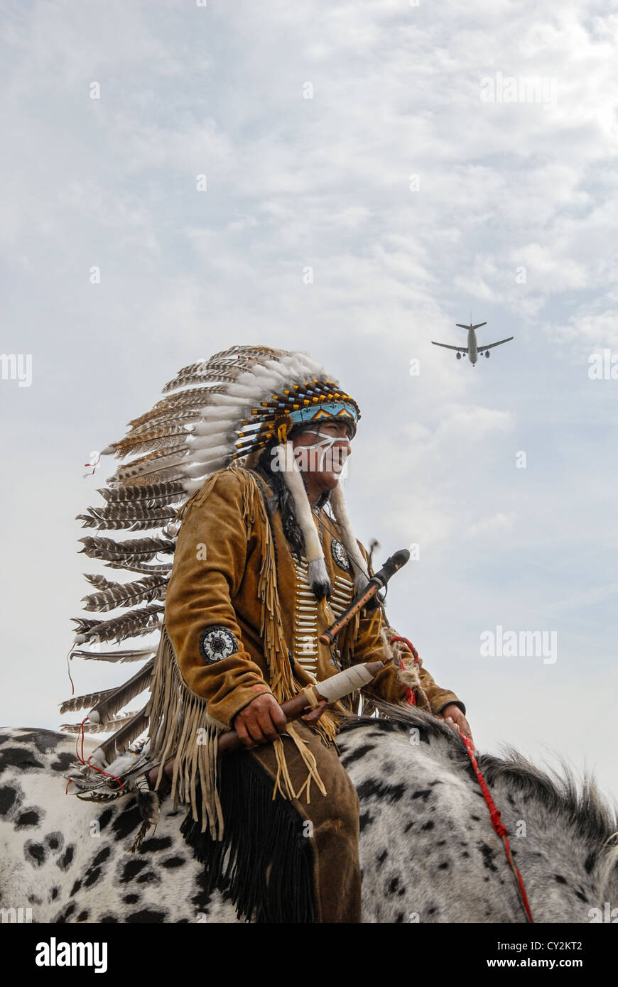 An airplane passes over a Native American in traditional dress - Stock Image