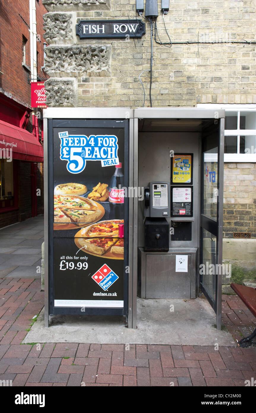 Advertising fast food products on UK public telephone kiosk - Stock Image