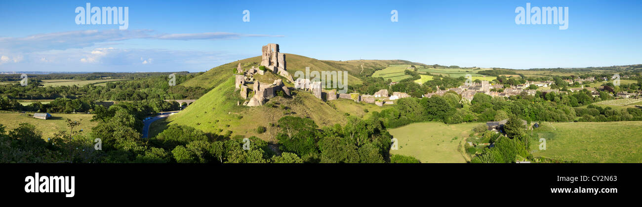 Stitched panorama of Corfe Castle on its hill above the beautiful Dorset countryside, and the village of Corfe Castle - Stock Image