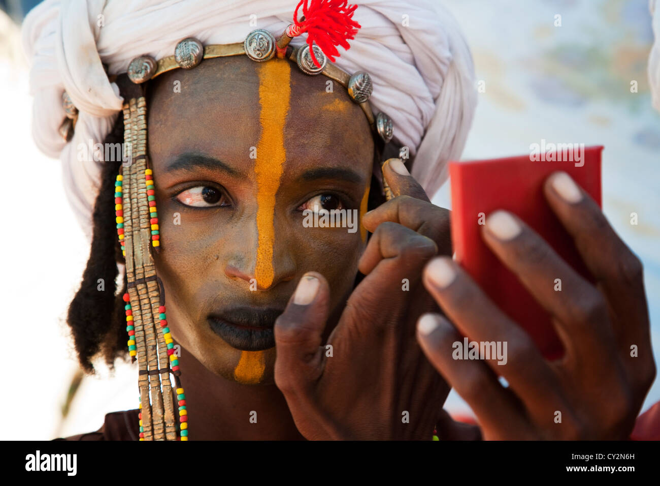 Wodaabe man is putting on make up in preparation for dancing at the geerewol festival in northern Niger, Africa Stock Photo