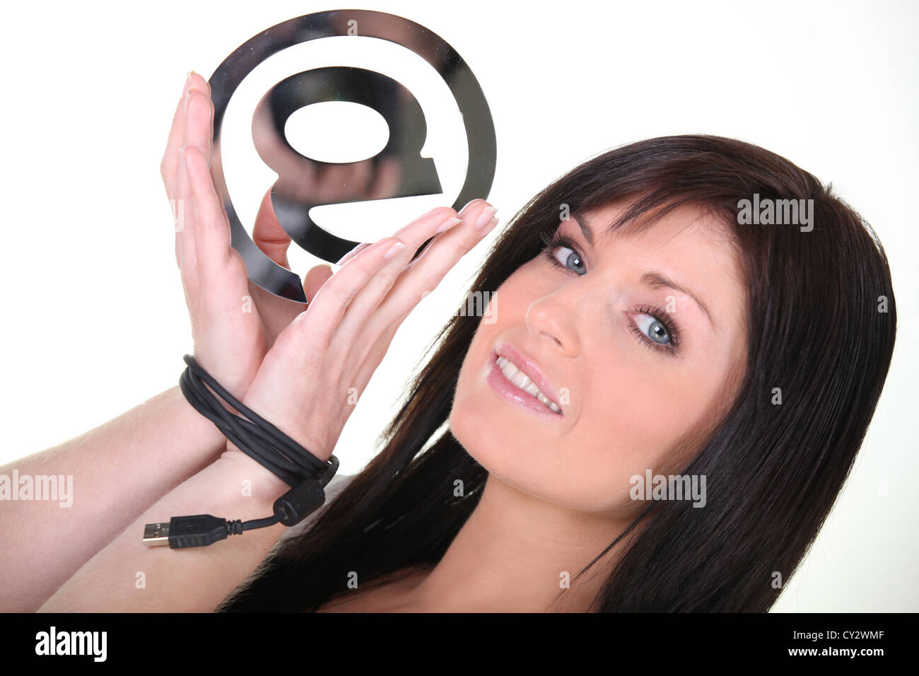 Woman holding an @ sign - Stock Image