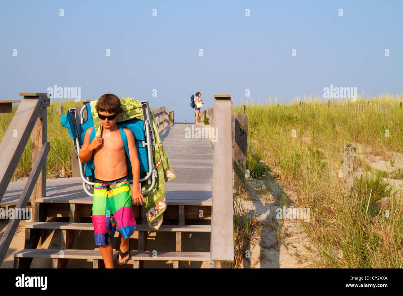 Massachusetts Cape Cod Nauset Beach Cape Cod National Seashore dune grass boardwalk sunbather boy sunglasses bathing - Stock Image