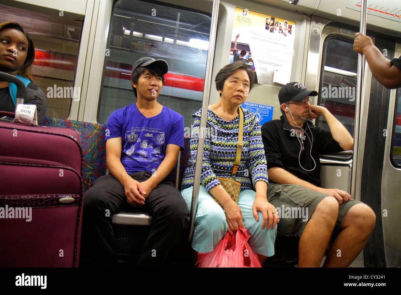 Boston Massachusetts South Boston MBTA T Red Line subway inbound train riders Asian man woman Black sitting - Stock Image