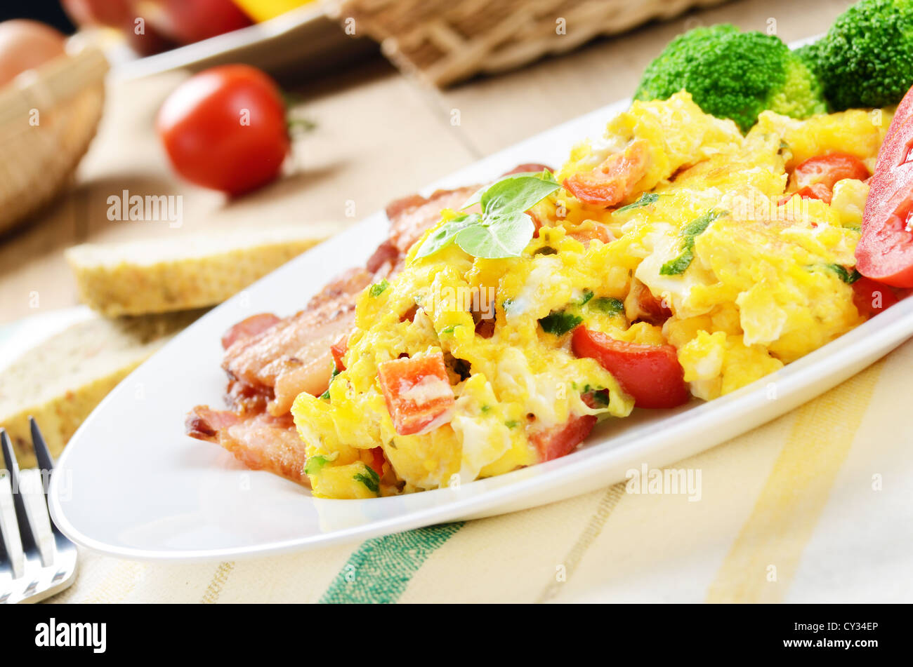 Omelet with vegetables, fried bacon and bread - Stock Image