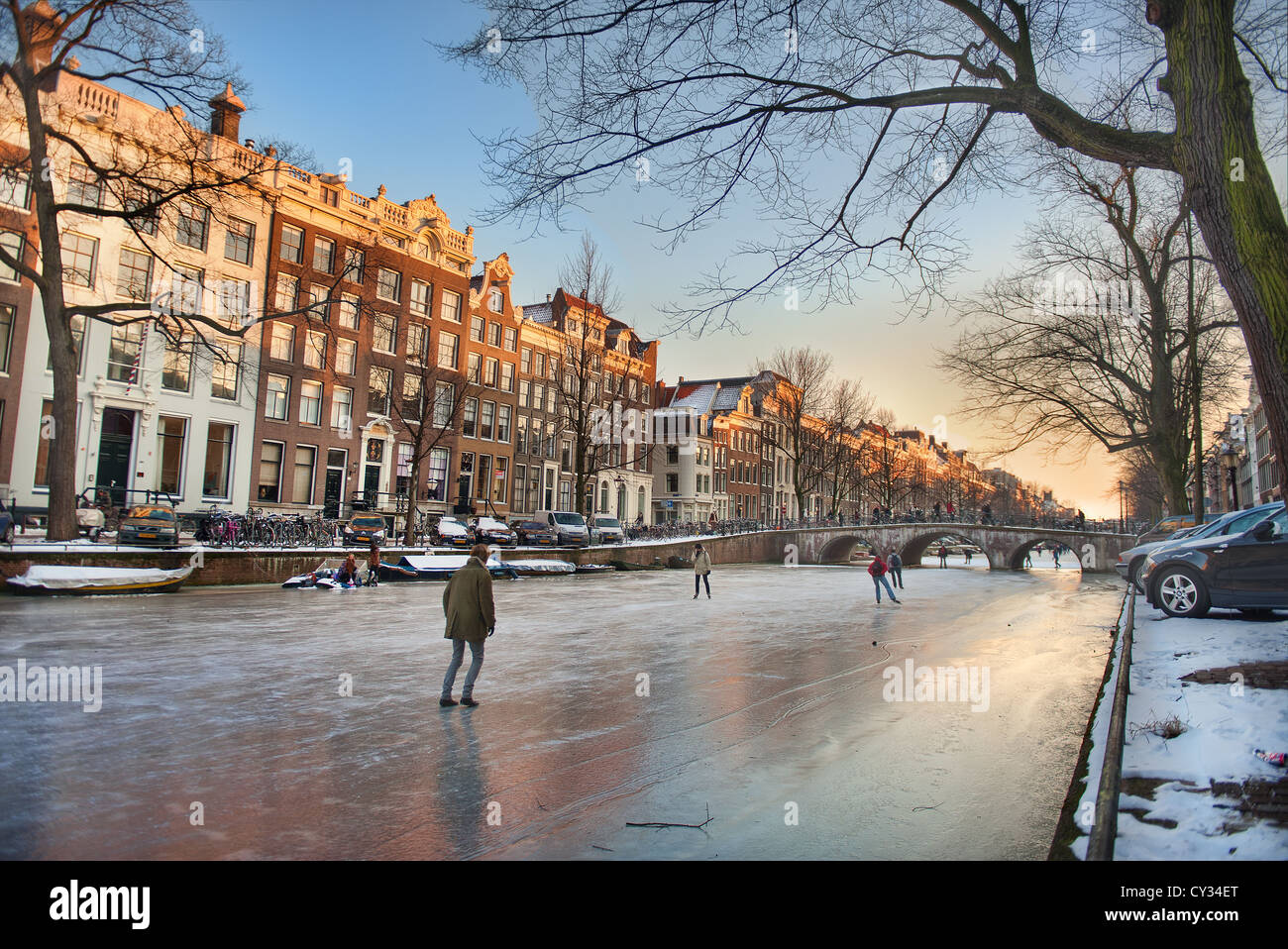 People skate on Amsterdam's frozen canals on a winter evening Stock Photo