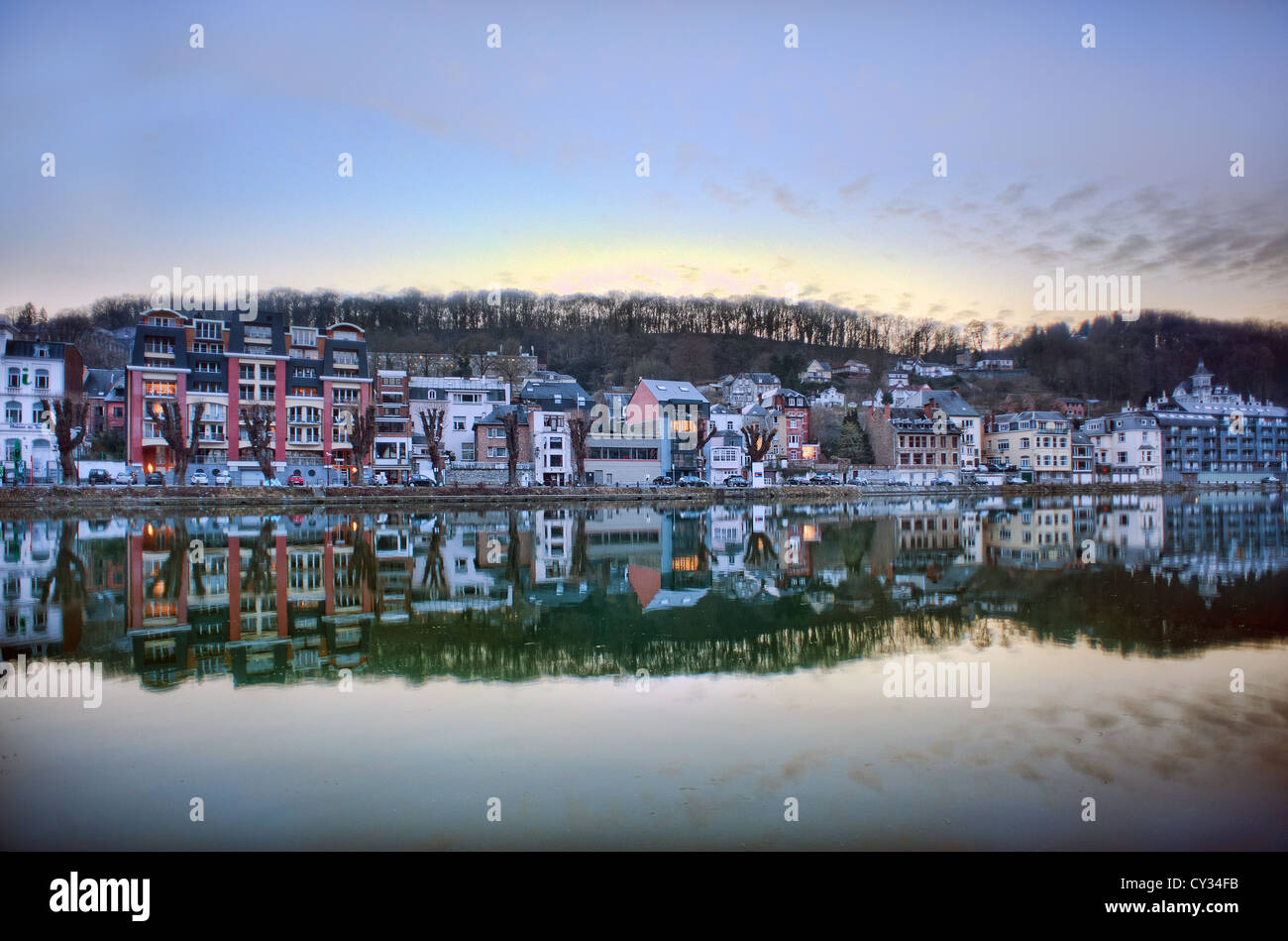 Houses and shops are reflected in the Meuse river at dusk in the Belgian town of Dinant in the Ardennes. - Stock Image