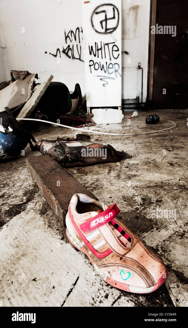 Pink and white sneaker left behind in a vandalized room after a fire destroyed the house - Stock Image