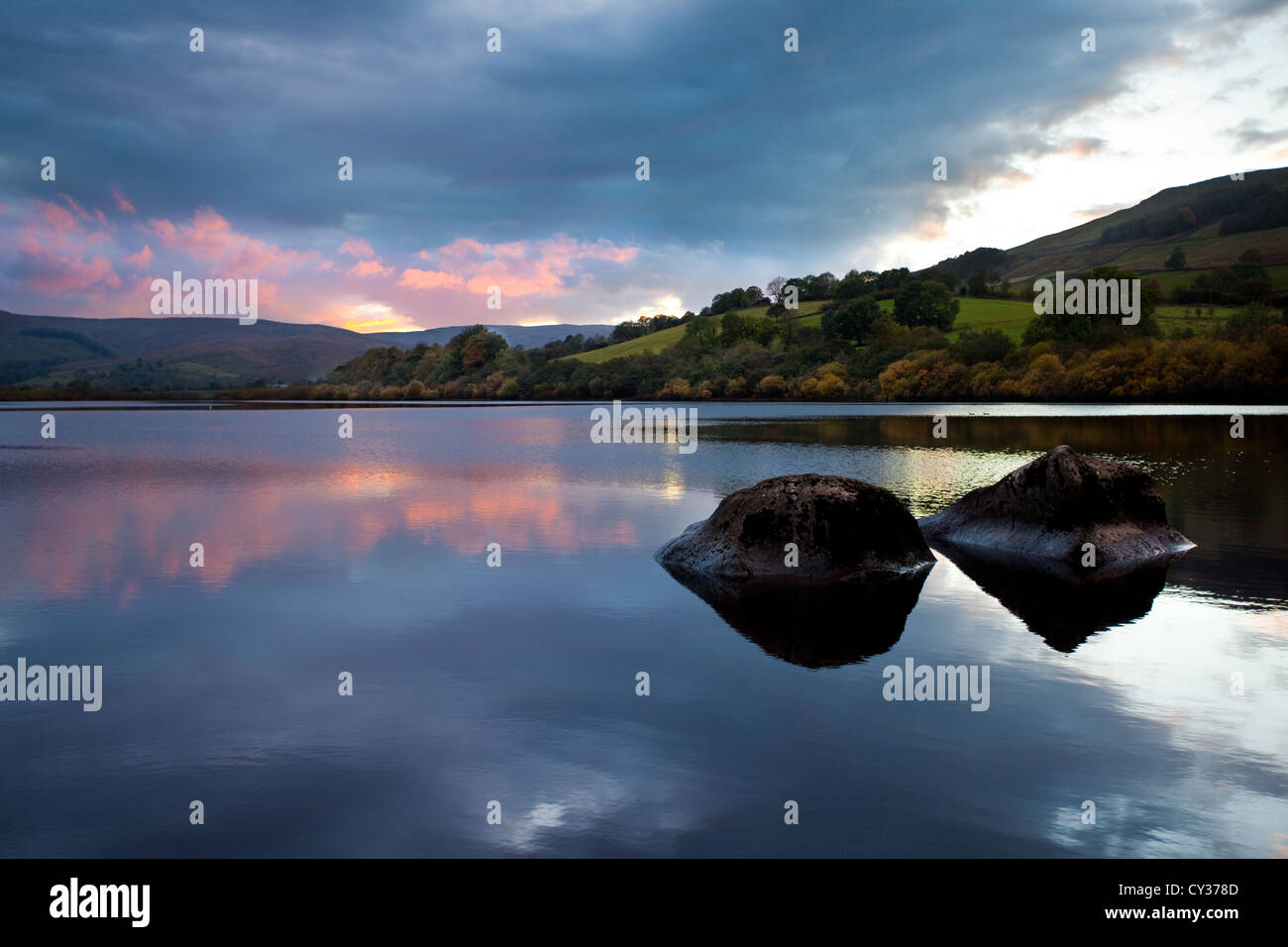 Placid lake on calm Autumn evening with sunset reflections over Lake Semerwater in Rydale, North Yorkshire Dales, - Stock Image