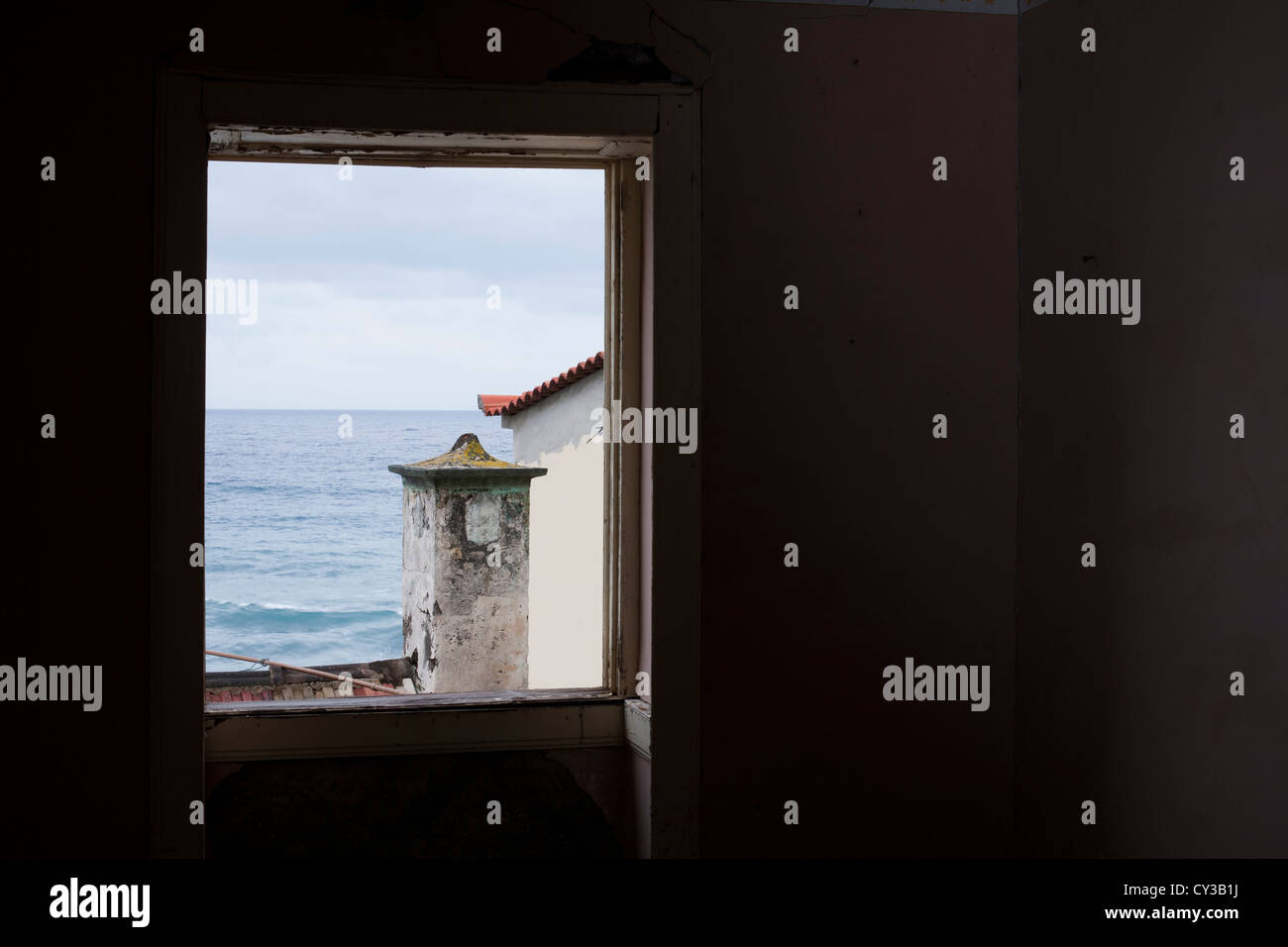 A view of the Atlantic Ocean from of the window of an abandoned house in the village of Jardim do Mar. Stock Photo