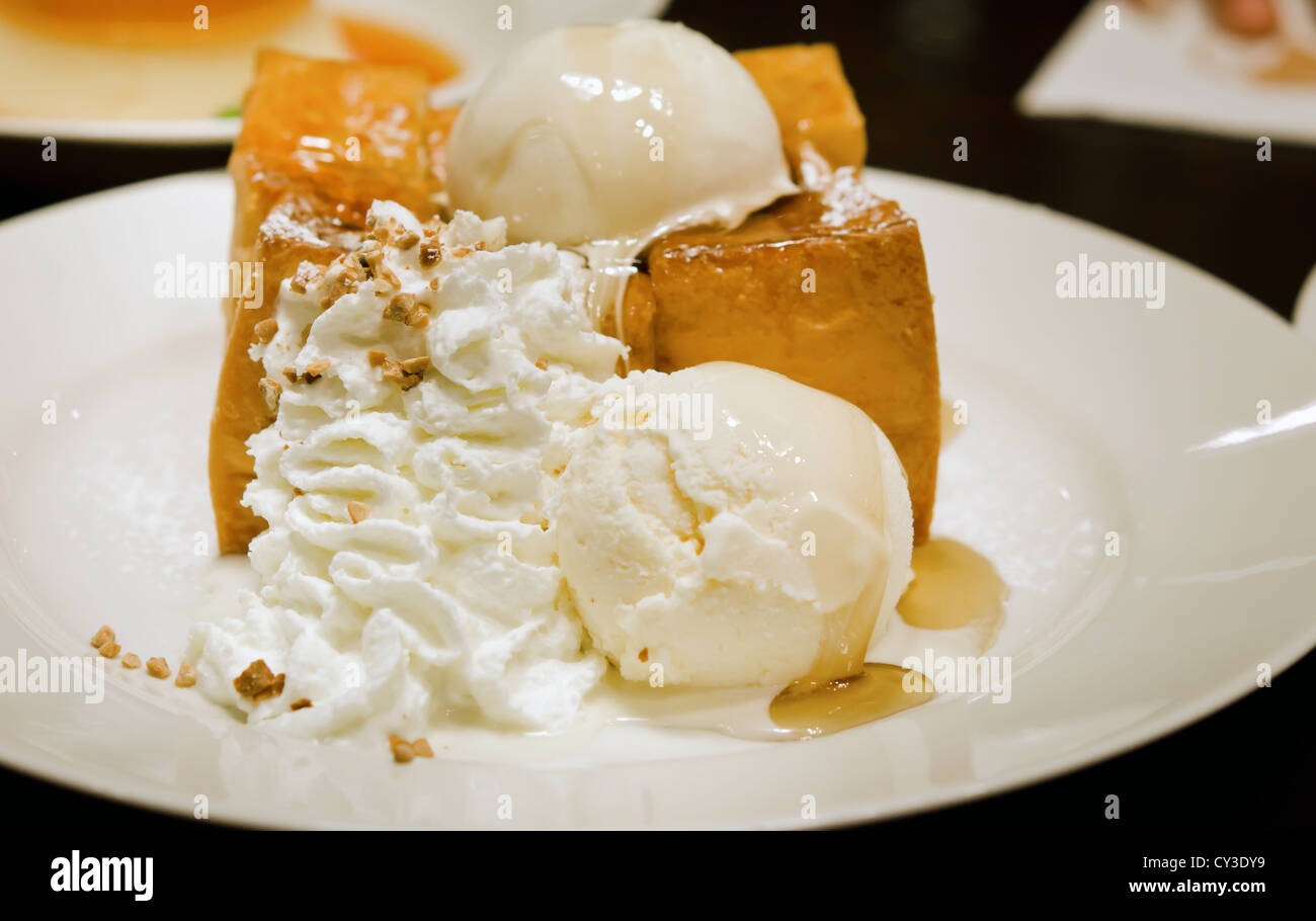 toast with ice cream ,whipping cream and honey syrup on white plate - Stock Image
