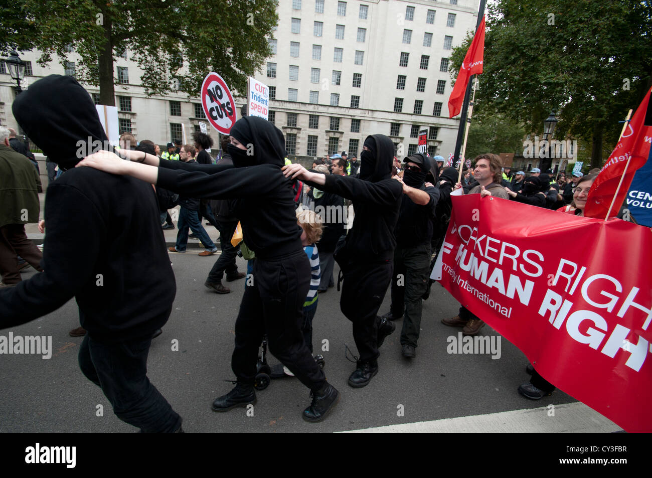 Black Bloc activists try to confuse the police as they weave their way through the TUC march on 20th October 2012 - Stock Image