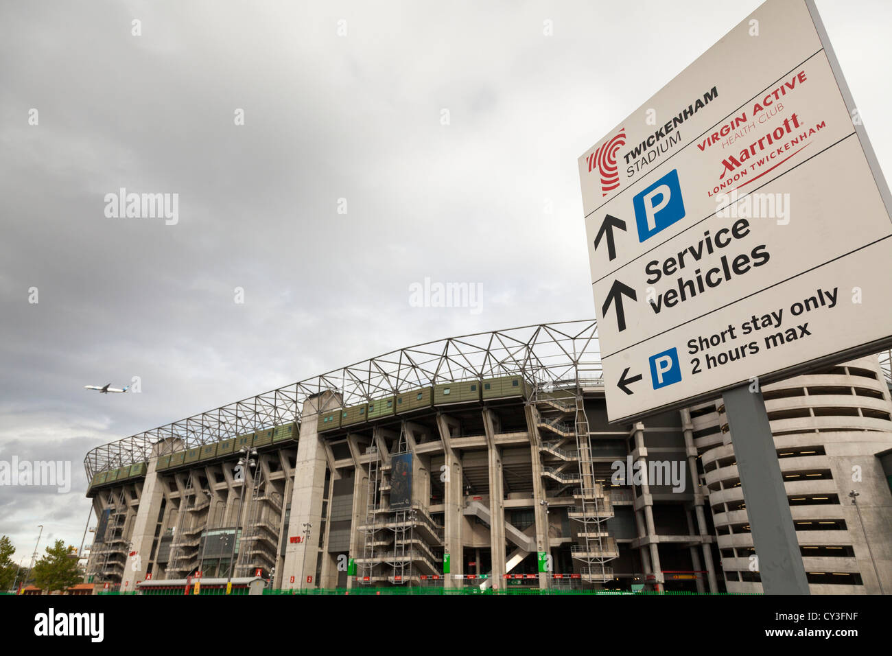 Twickenham stadium with parking information sign and aircraft. - Stock Image