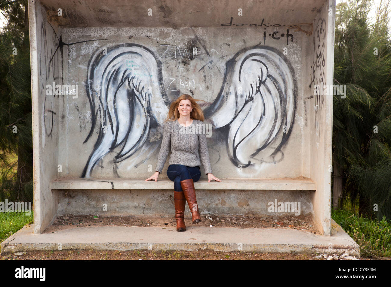 Blond haired woman sitting at bus stop with graffiti angel wings. - Stock Image