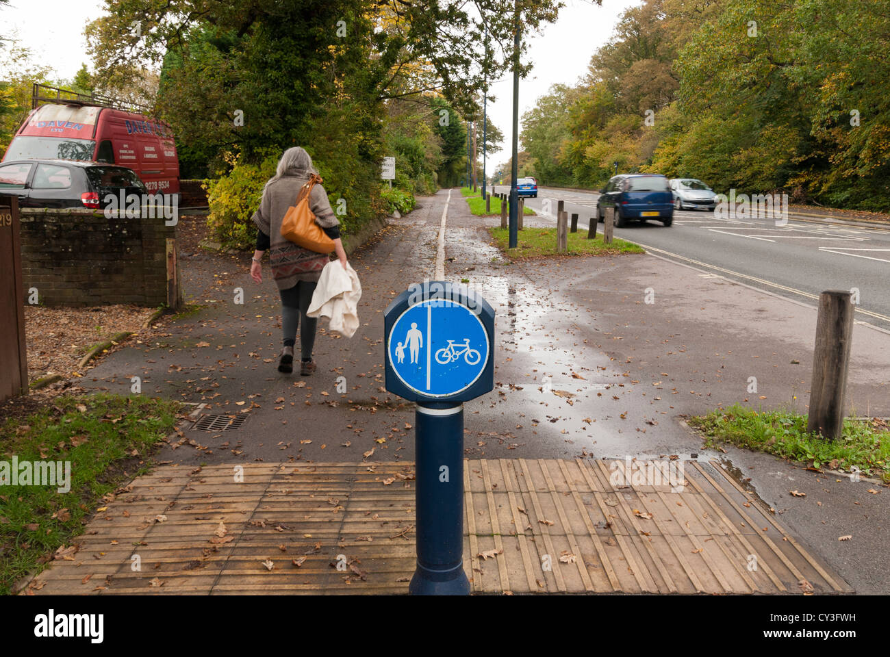 pedestrian cycle way dividing sign on shared footpath alongside road - Stock Image