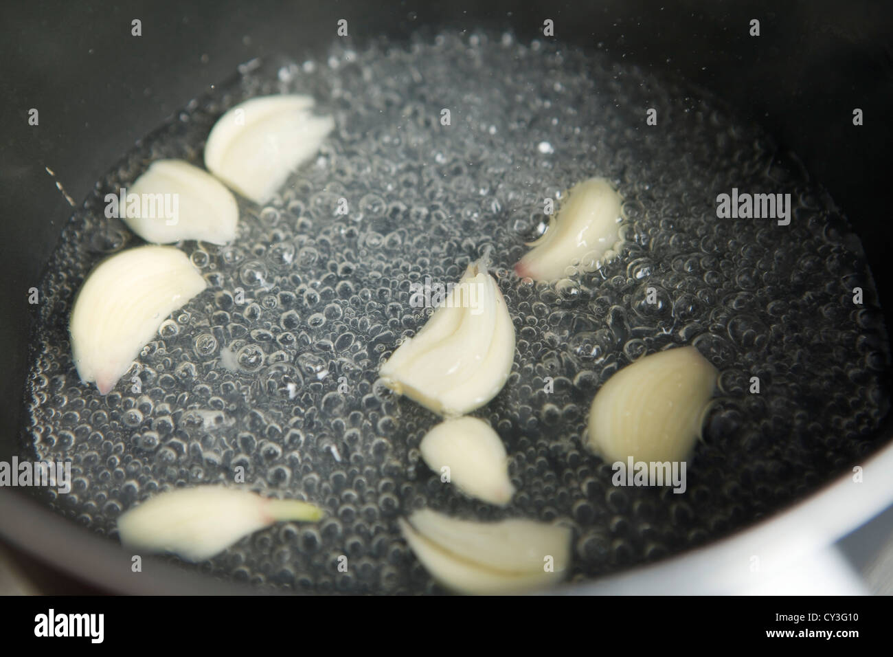 Simmering garlic cloves in water. - Stock Image