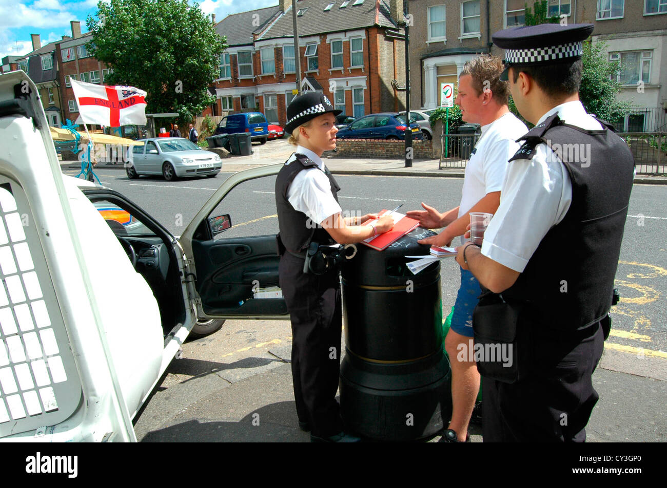 A policewoman writes down the details of a motorist after the stop and search of a van in Bounds Green, north London. - Stock Image
