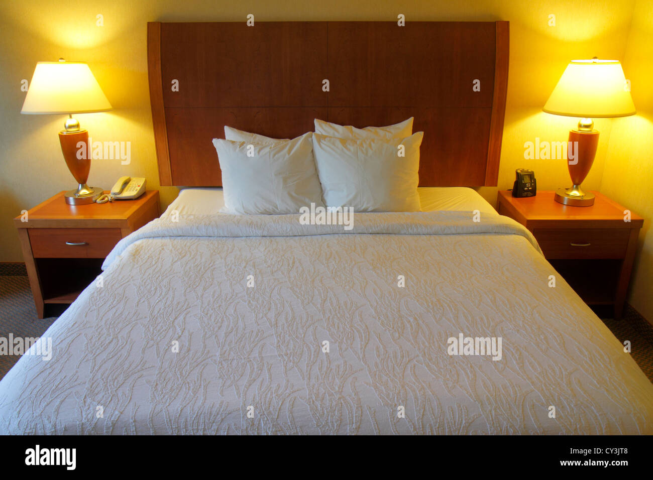Maine Freeport Hilton Garden Inn motel hotel guest room queen-size bed made pillows lamps tables headboard - Stock Image