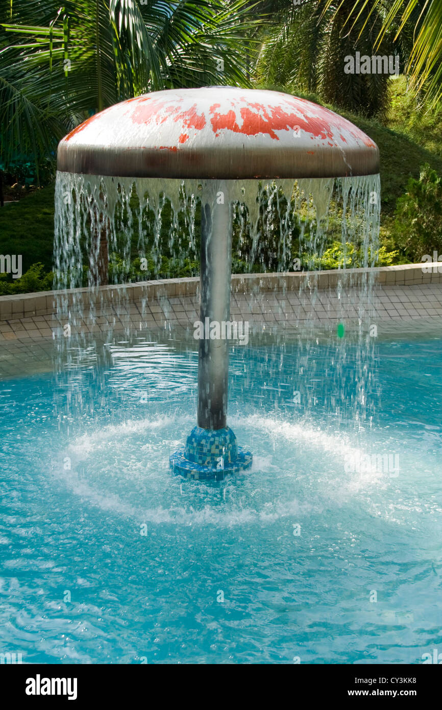Circle of dripping water from umbrella in a recreation swimming pool ...
