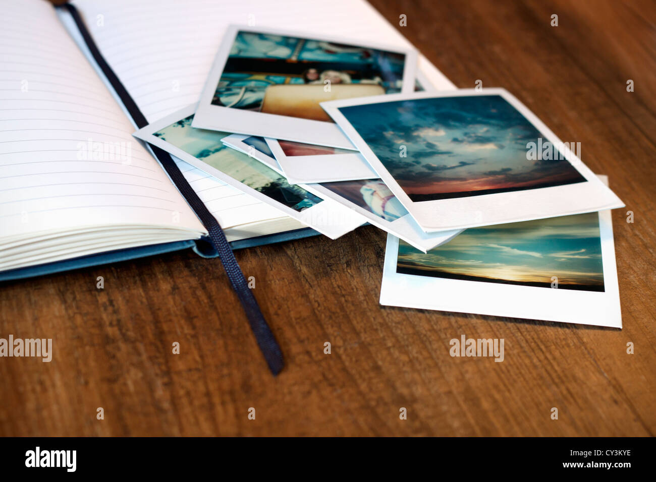 Vintage polaroid pictures and an open journal. - Stock Image