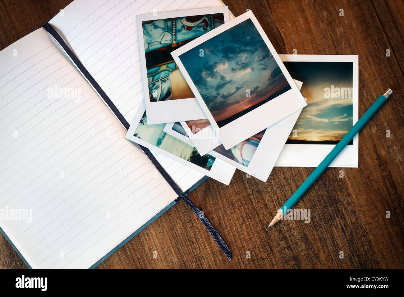 Vintage polaroid pictures, an open journal and pencil. - Stock Image