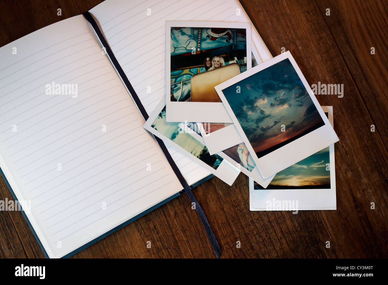 Polaroid pictures lying on top of a journal. - Stock Image