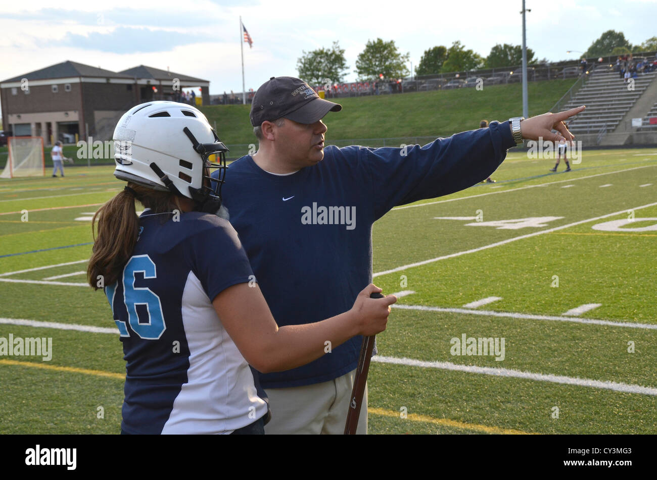 Coach making strategic suggestions to his player in a girls lacrosse game in Edgewater, Maryland - Stock Image