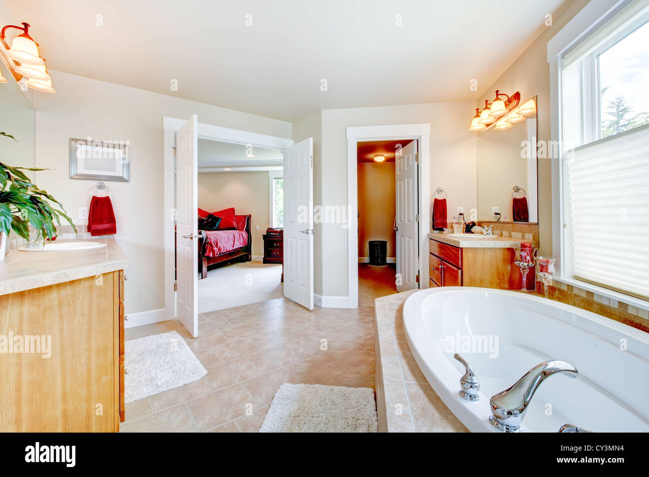Large bathroom with white tub and open door to bedroom and closet ...