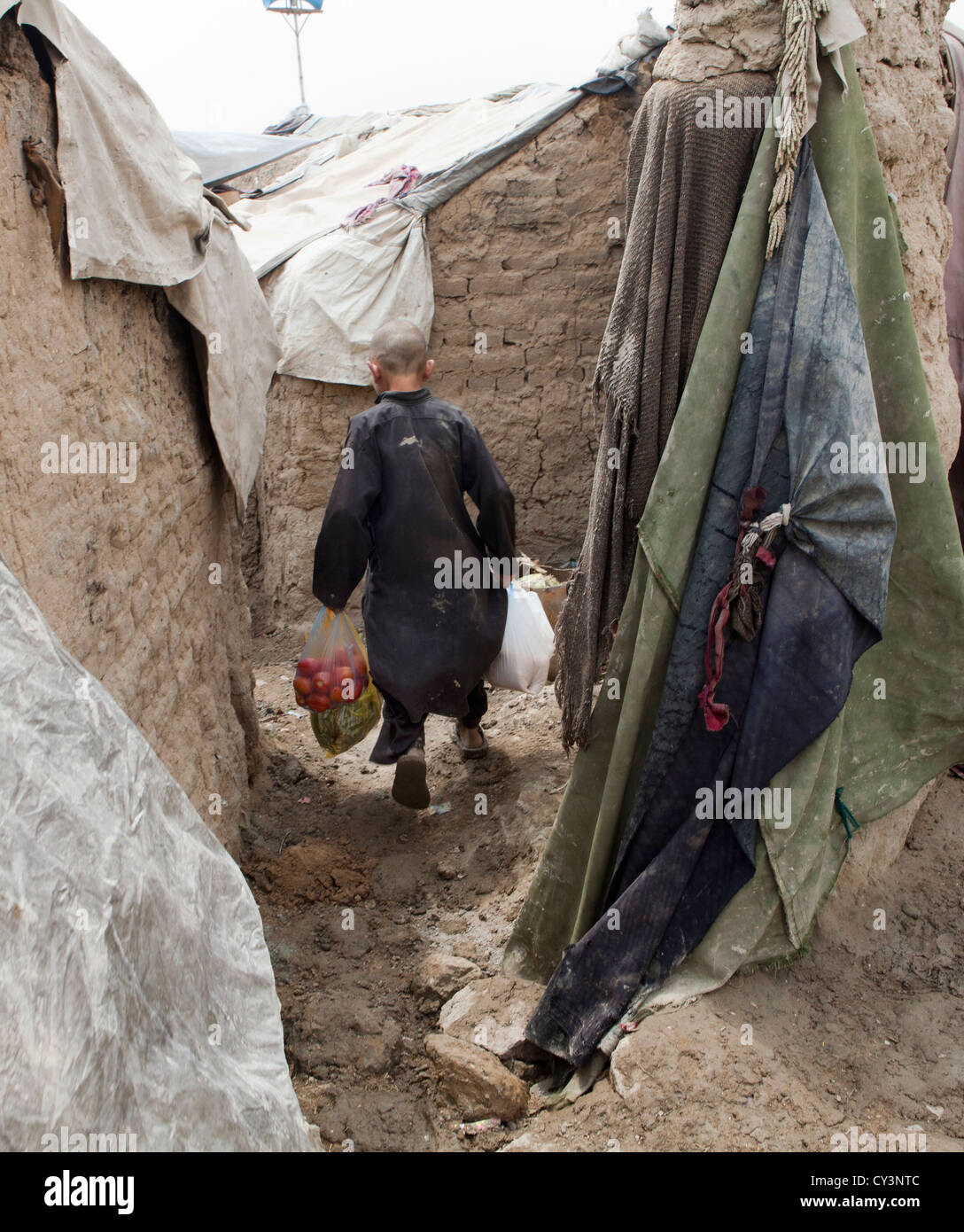 refugeeboy in kabul going home with food - Stock Image