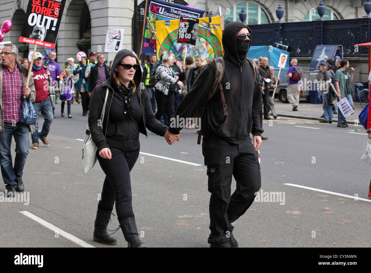 Black bloc flag anarchist protester couple at Anti-Austerity March, Piccadilly central London, UK. A Future That - Stock Image
