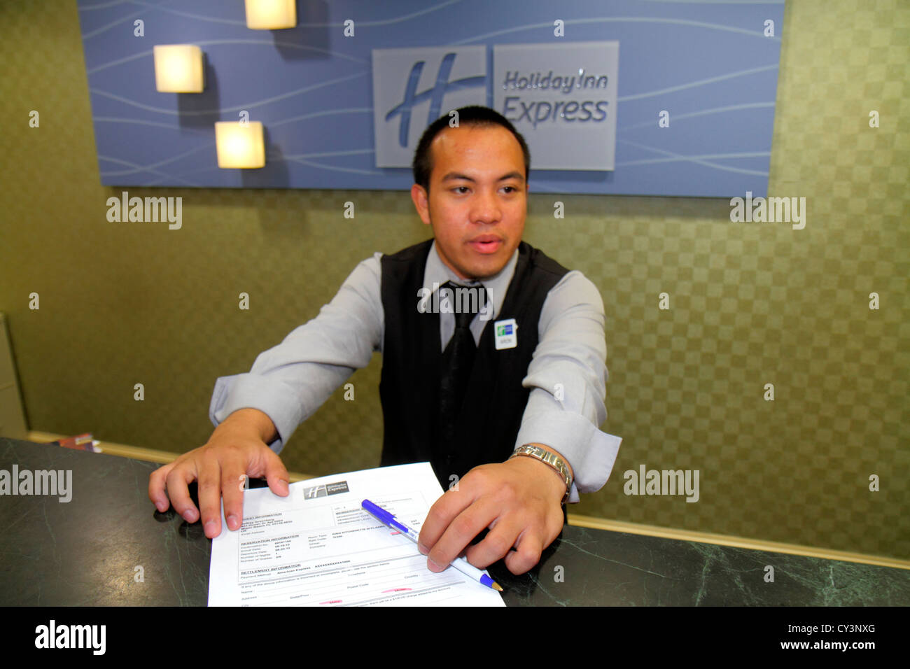 Rhode Island Newport Middletown Holiday Inn Express motel hotel front desk lobby Asian man employee clerk service - Stock Image