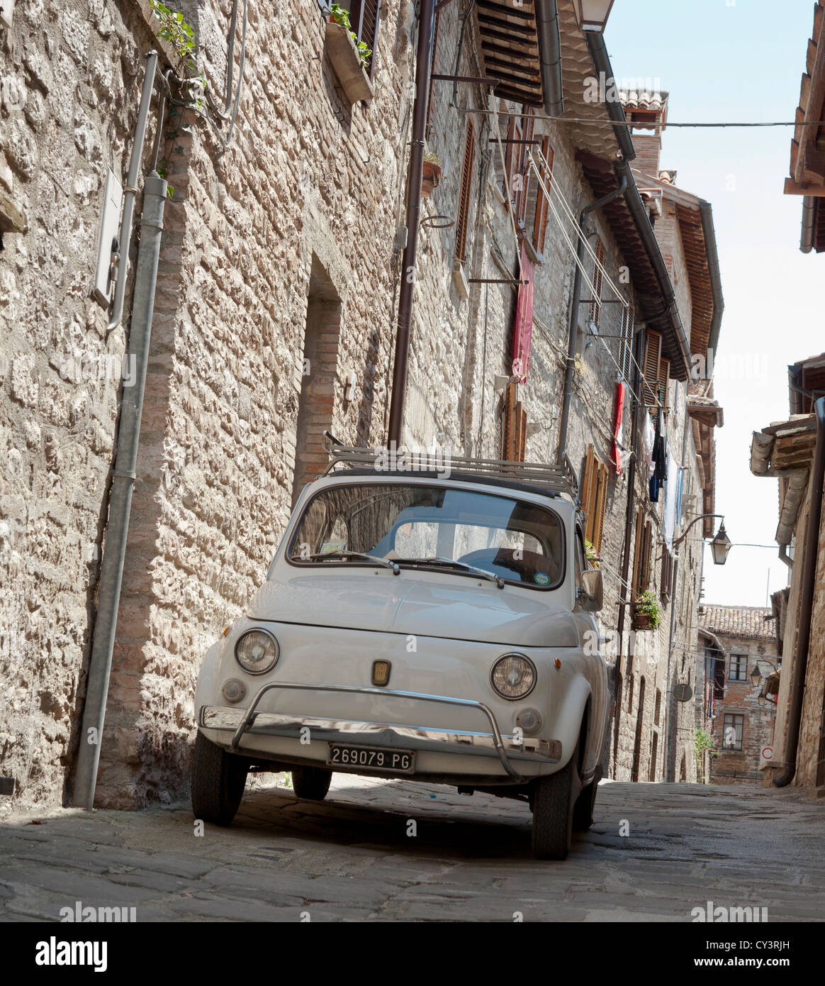 Small Fiat Car In Narrow Cobbled Guubbio Street Umbria Italy Stock