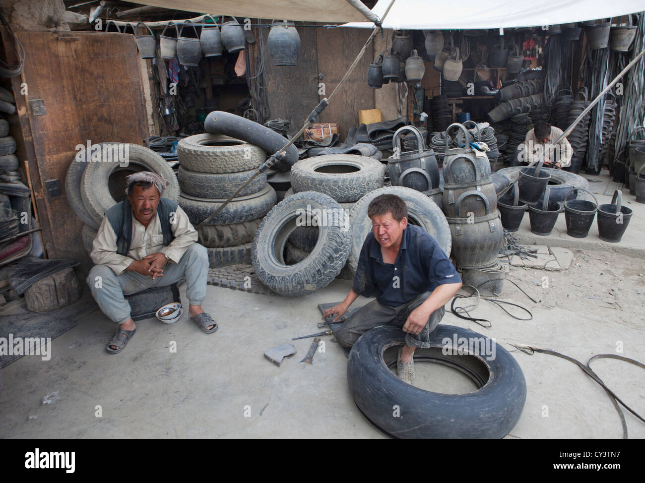 afghan man makes snadals from old tires in kabul - Stock Image