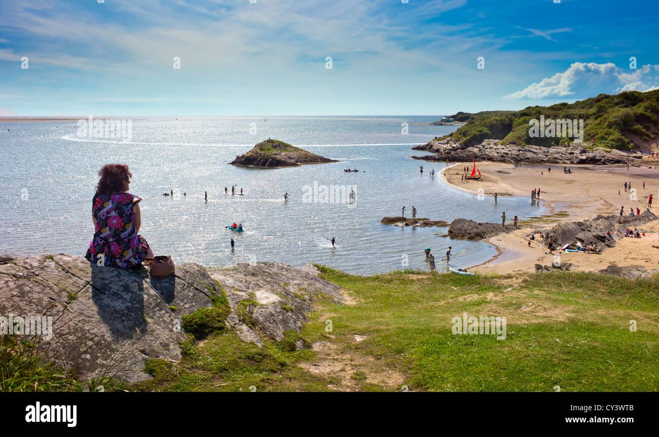 adult female looks down on a small sandy bay, children in the sea, families on the beach, enclosed by shrub covered - Stock Image