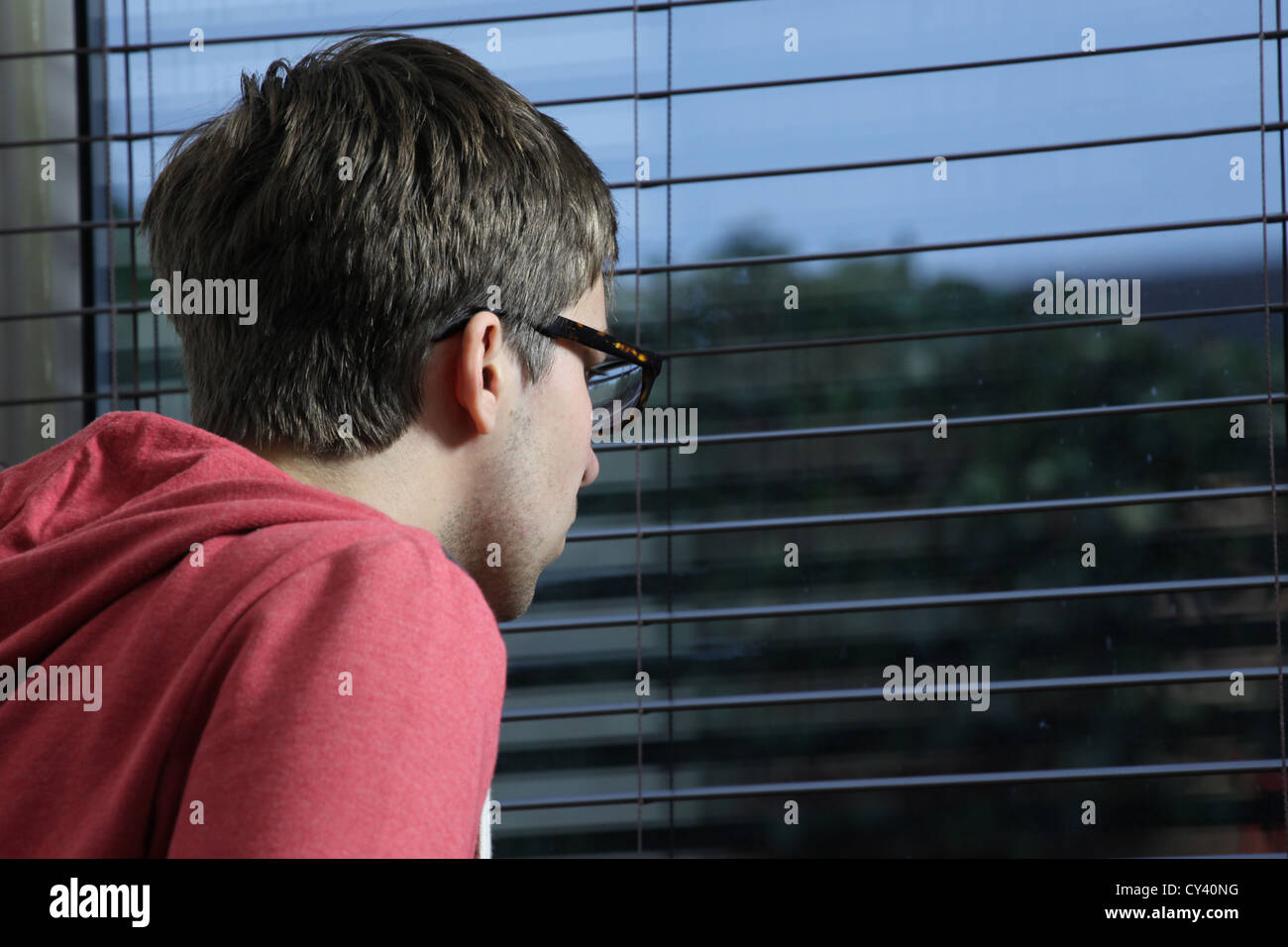 Young man wearing glasses, looking through a window blind. - Stock Image