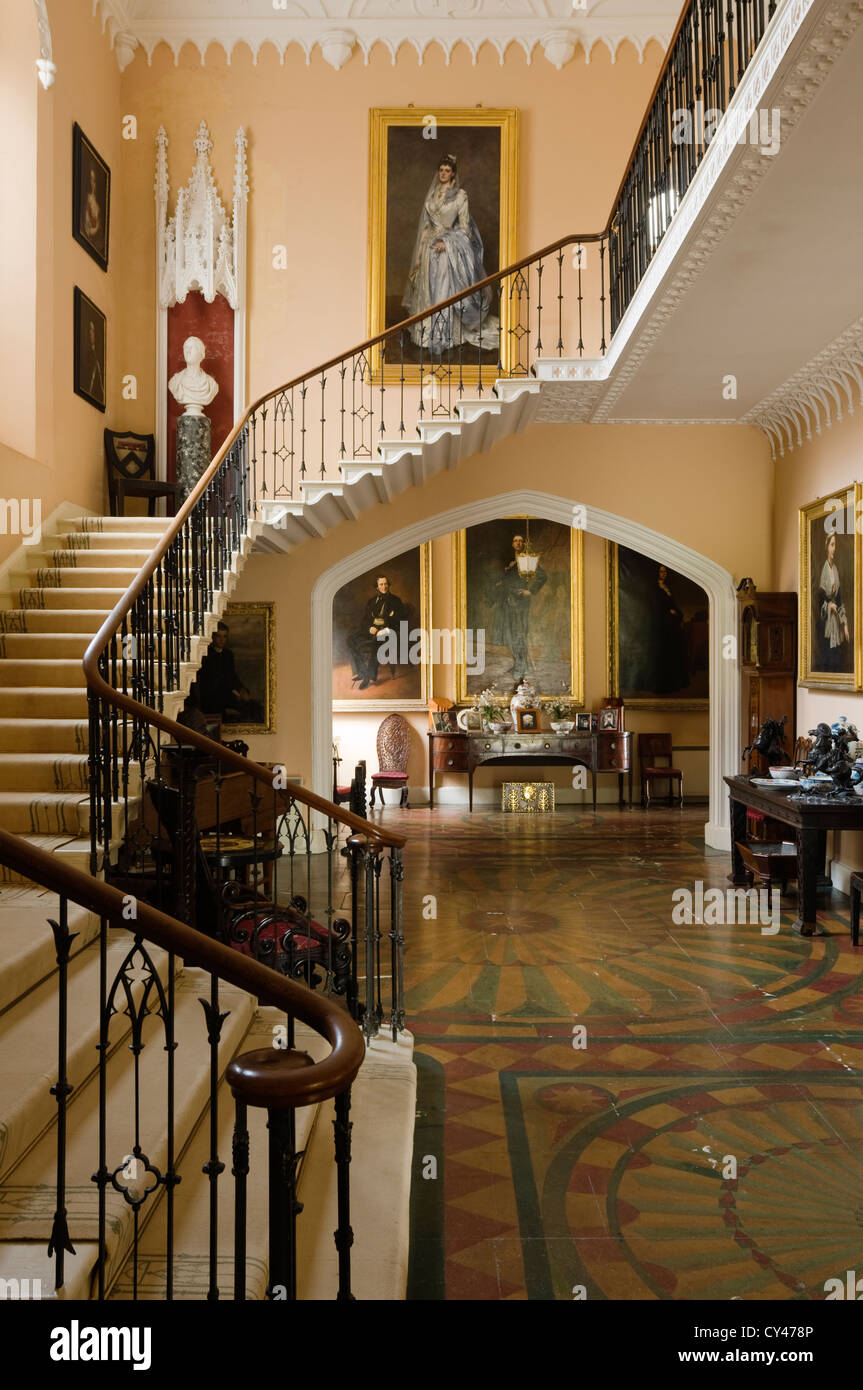 Staircase in entrance hall with original floor tiles and full length paintings - Stock Image