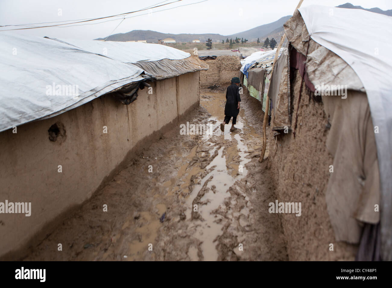 Afghan boy walking in a slum of kabul - Stock Image